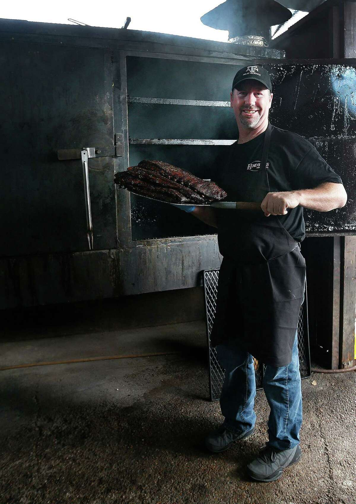 Russel Roegels pulls ribs out of his pits at Roegels Barbecue Co. on Voss, Thursday, April 16, 2015, in Houston. ( Karen Warren / Houston Chronicle )
