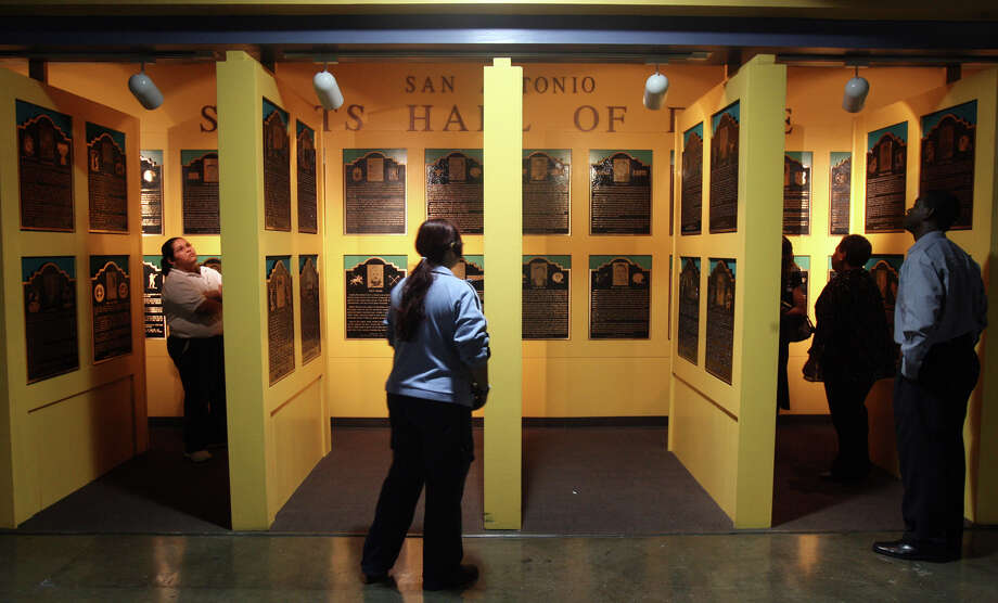 People look at the plaques of inductees to the San Antonio Sports Hall of Fame on Tuesday October 9, 2007 at the Alamodome before the announcement of who the 2008 inductees will be. The 2008 inductees are: football player Lyle Blackwood, coach and athletic director Jerry Comalander, Olympic medalist Josh Davis, track sprinter and football player Clyde Glosson, and baseball player Clifford Johnson. Photo: Express-News File Photo / SAN ANTONIO EXPRESS-NEWS