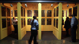 People look at the plaques of inductees to the San Antonio Sports Hall of Fame on Tuesday October 9, 2007 at the Alamodome before the announcement of who the 2008 inductees will be. The 2008 inductees are: football player Lyle Blackwood, coach and athletic director Jerry Comalander, Olympic medalist Josh Davis, track sprinter and football player Clyde Glosson, and baseball player Clifford Johnson.