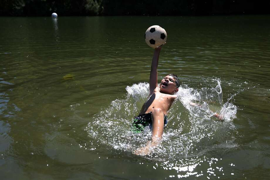 Jovanni Giovanni, 8, of Pacifica plays with a soccer ball in the Russian River during a trip out with his mother and sister to Johnson's Beach in Guerneville, California, Friday, September 4, 2015. A potentially harmful blue-green algae has been detected in the Russian River. Authorities are considering closing beaches and advising people to stay out of the river over the holiday weekend. A dog that came in contact with the poisonous algae died on Thursday, and two other dogs suspected of suffering a similar fate earlier this summer. Ramin Rahimian/Special to The Chronicle Photo: Ramin Rahimian, Special To The Chronicle