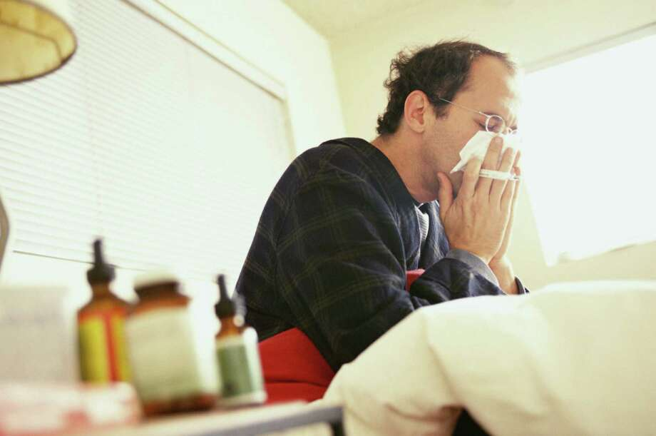 Man sick in bed blowing his nose. Photo: Marc Romanelli, Getty Images / (c) Marc Romanelli