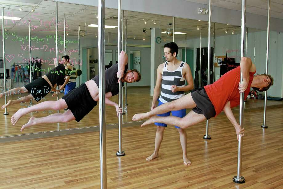 Instructor Patrick Alvarez, center, works with students Robert Trimmer, left, and Stephen Andrews on a move called a flag, during a man's pole dance class at Verticality Pole Fitness.  (For the Chronicle/Gary Fountain, August 29, 2015) Photo: Gary Fountain, Freelance / Copyright 2015 by Gary Fountain