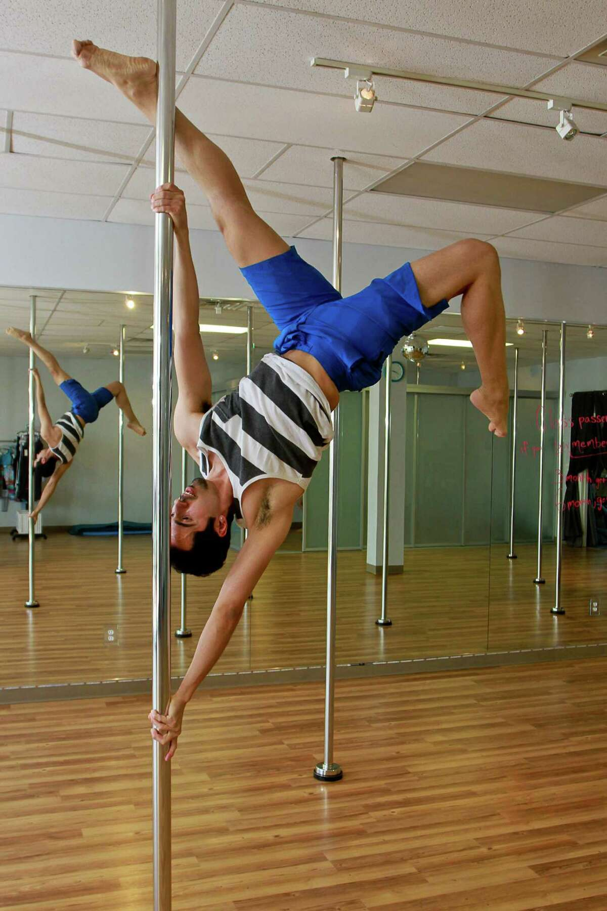 Instructor Patrick Alvarez demonstrates an extended butterfly move during his pole-dancing class.