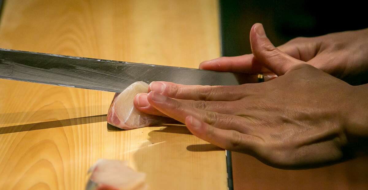 Chef Ingi Son cuts fish at Omakase in San Francisco, Calif., on September 3rd, 2015.