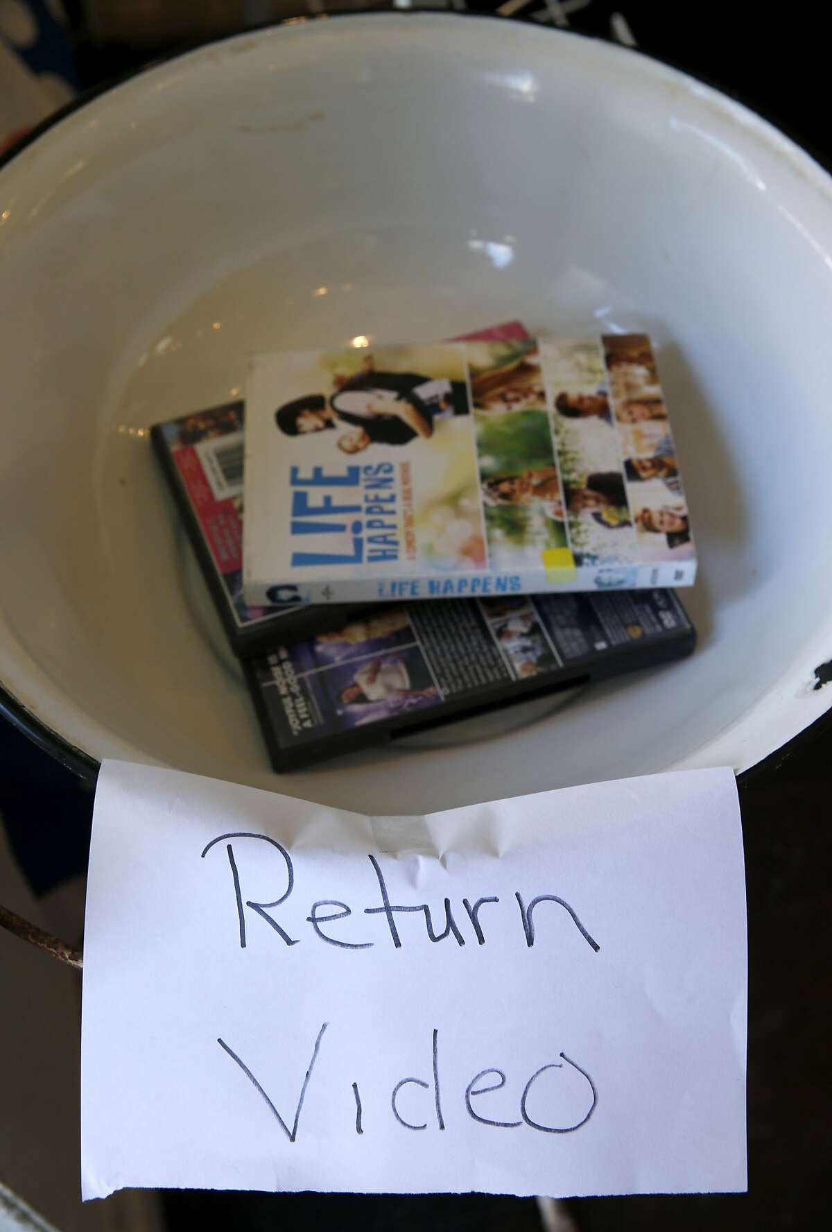Rentals are returned to a metal wash basin at the new Noe Valley location of Video Wave video rental shop in San Francisco, Calif. on Friday, Sept. 4, 2015. Believed to be the oldest video rental business in the city, Video Wave now shares the back end of a candy store after its lease expired at the original location around the corner.