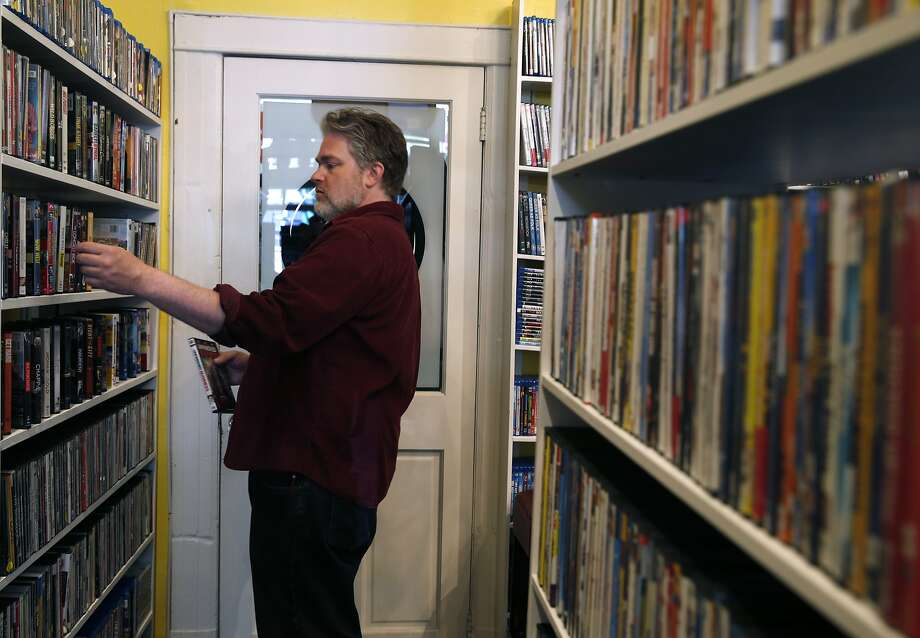 Video Wave of Noe Valley rental shop co-owner Colin Hutton arranges shelves of DVDs at its new location on 24th Street. Photo: Paul Chinn, The Chronicle