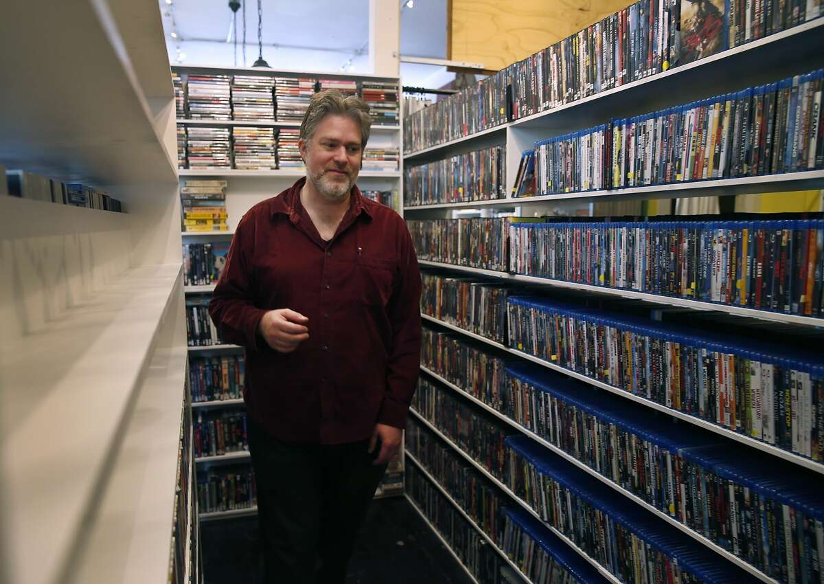Video Wave video rental shop co-owner Colin Hutton arranges shelves of DVDs at its new Noe Valley location on 24th Street San Francisco, Calif. on Friday, Sept. 4, 2015. Believed to be the oldest video rental business in the city, Video Wave now shares the back end of a candy store after its lease expired at the original location around the corner.