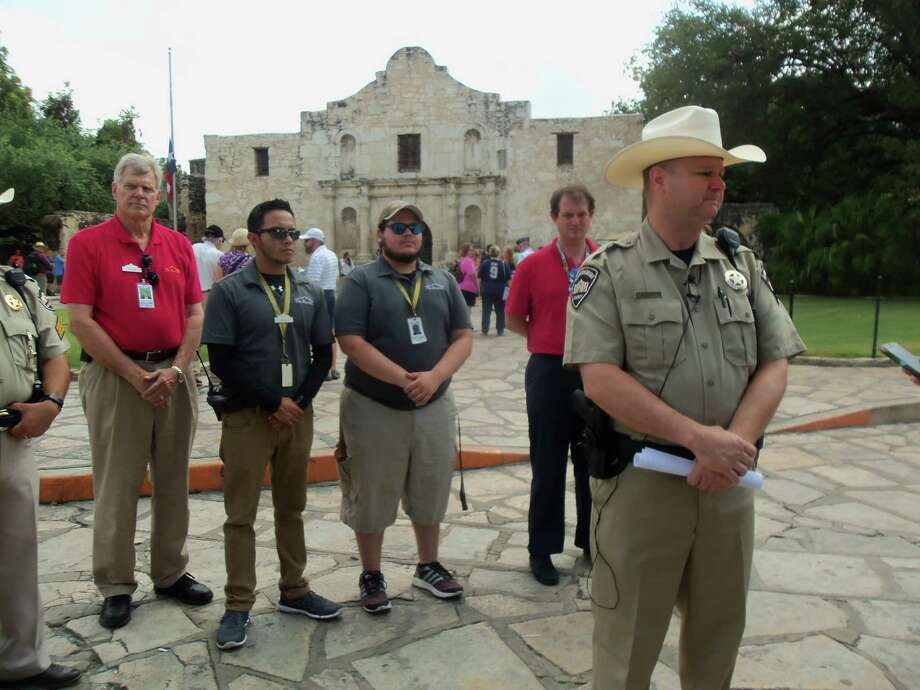 Alamo Rangers Chief Mark Adkins speaks Friday to the media about Thursday's desecration of part of a wall in the mission-era church, with tour guides and other employees at the state shrine behind him. Photo: SCOTT HUDDLESTON /SAN ANTONIO EXPRESS-NEWS