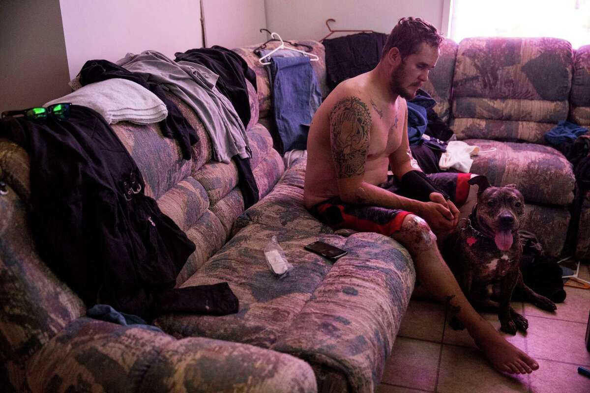 Devin Meurer sits with his dog Rocco in his apartment in Pleasanton, Texas on August 6, 2015. Meurer is facing eviction after getting in a motorcycle accident and losing his third job since December, 2014. The dramatic drop in oil prices has sent investors running scared and forcing companies to lay off workers and slash pay. Rocco unexpectedly died several weeks ago.