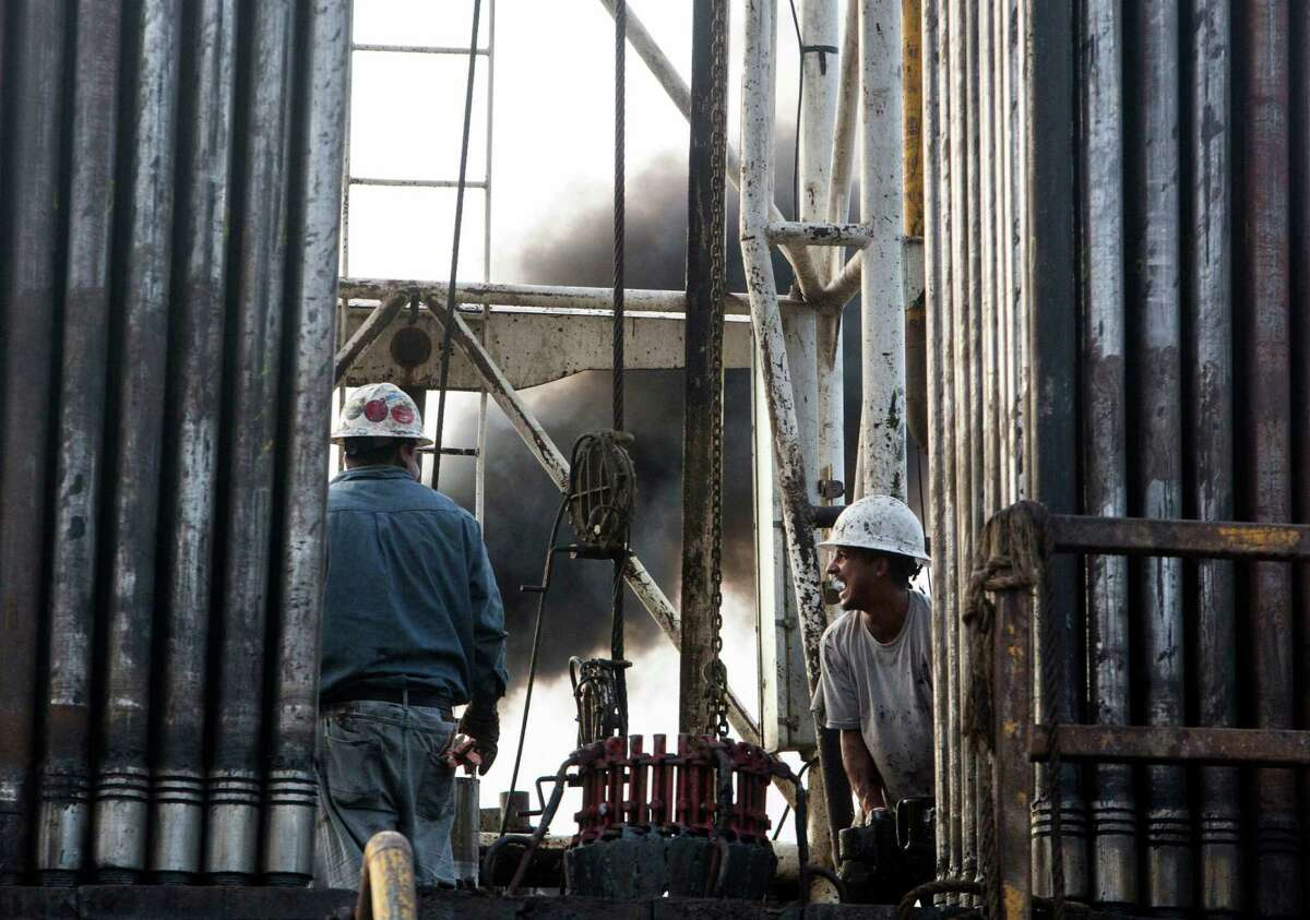 Oil field workers stand next to drilling collars on an oil rig in Hallettsville, Texas on May 22, 2015.