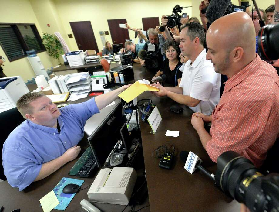 Rowan County deputy clerk Brian Mason presents James Yates and his partner William Smith Jr. their marriage license on Friday in Morehead, Ky., after the couple had been denied four times. Photo: Timothy D. Easley, FRE / FR43398 AP