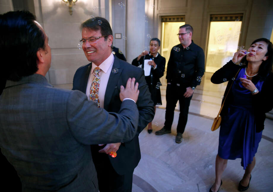 "Newlyweds Peter Shields (left) and Raul Hernandez embrace after exchanging vows at San Francisco City Hall as friend Robin Nakamura blows bubbles. ""It is a demonstration of my full commitment to him,"" Hernandez said. Photo: Paul Chinn / Photos By Paul Chinn / The Chronicle / ONLINE_YES"