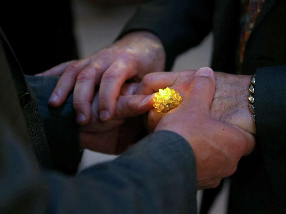 Raul Hernandez and Peter Shields exchange illuminated rings during their wedding ceremony. Photo: Paul Chinn / Paul Chinn / The Chronicle / ONLINE_YES