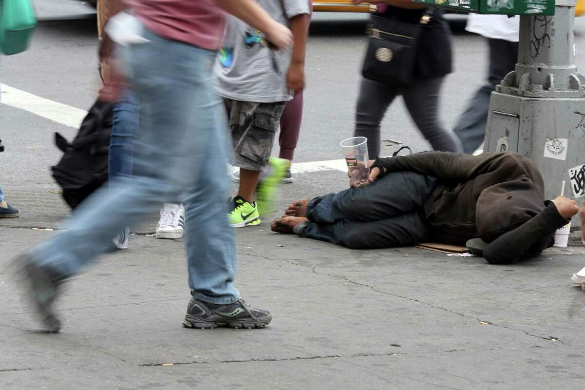 People walk past a homeless man asking for money on 14th Street, Friday, Sept. 4, 2015, in New York. The number of homeless on New York City's streets has increased, prompting breathless media coverage and worries that the