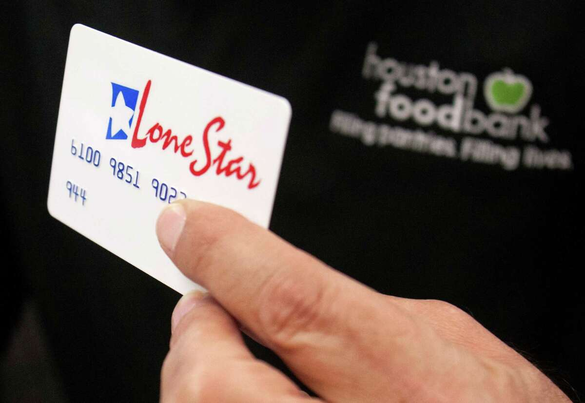 A Lone Star card is presented as Houston Food Bank Social Service coordinators help register clients for SNAP.