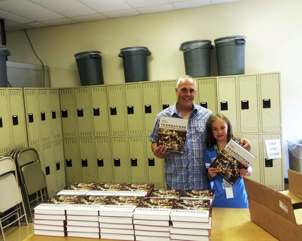 Capital Region BOCES Career and Technical School chef and teacher Paul Rother returned to the classroom on Monday to prepare for the school year which begins next week. His daughter Olivia lent him a hand unpacking new text books and preparing the room. (Mike McCagg)