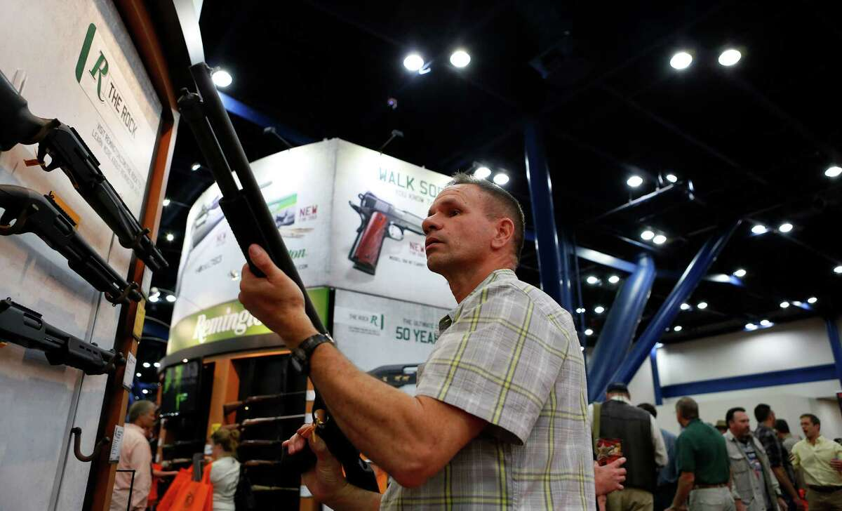 An NRA attendee looks through the scope of a Freedom Group Inc. Remington brand gun during the 2013 National Rifle Association Annual Meetings & Exhibits at the George R. Brown Convention Center in Houston, Texas, U.S., on Saturday, May 4, 2013. After the U.S. Senate defeated a proposed expansion of background checks on gun purchases, the NRA's annual conference has a celebratory atmosphere. Yet as the festivities began, gun-control advocates swarmed town halls, organizing petitions and buying local ads to pressure senators from Alaska to New Hampshire to reconsider the measure that failed by six votes on April 17. Photographer: Aaron M. Sprecher/Bloomberg