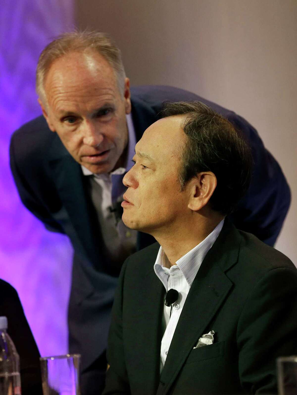 Kiyotaka Ise, Senior Managing Officer for Toyota Motor Corporation, bottom, listens to Chuck Gulash, Toyota Senior Executive Engineer, during a news conference in East Palo Alto, Calif., Friday, Sept. 4, 2015. Toyota announced it is investing $50 million with Stanford University and the Massachusetts Institute of Technology in hopes of gaining an edge in an accelerating race to phase out human drivers. (AP Photo/Jeff Chiu) ORG XMIT: CAJC102