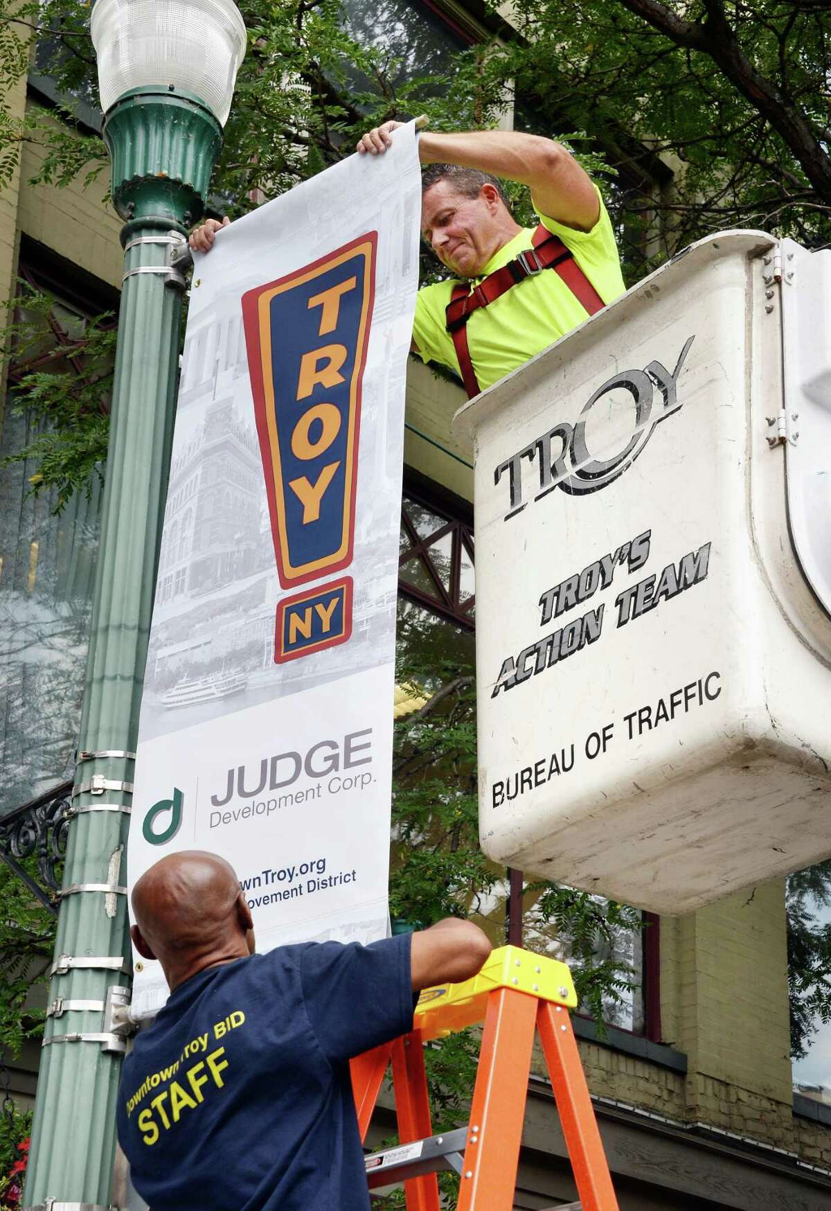 Traffic department's Bill Wangler, top, and Troy BID's Daryl Evans hang the first of 100 new style street banners at Monument Square Friday Sept. 4, 2015 in Troy, NY. (John Carl D'Annibale / Times Union)