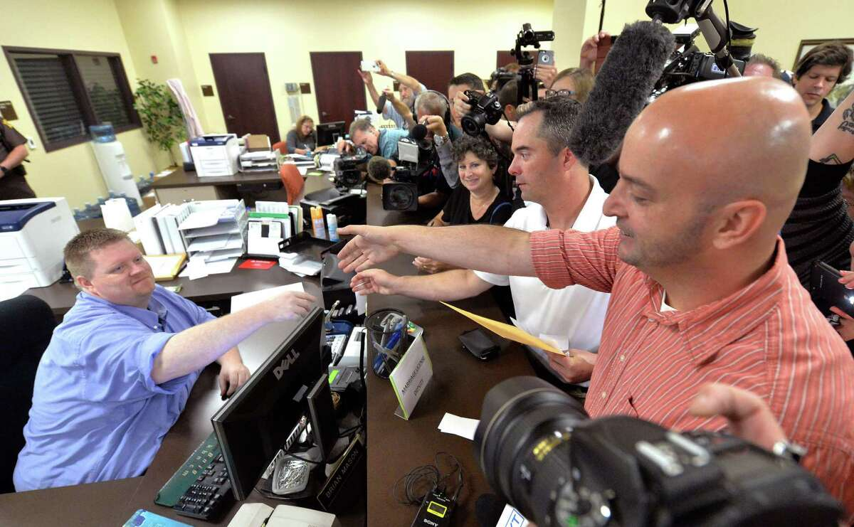 Rowan County deputy clerk Brian Mason, left, shakes hands with James Yates and his partner William Smith Jr. after issuing their their marriage license at the Rowan County Judicial Center in Morehead, Ky., Friday, Sept. 4, 2015. After four attempts, Yates and Smith were the first gay couple to receive their marriage license, hours after the county's defiant clerk was hauled to jail for refusing to license same-sex marriages. (AP Photo/Timothy D. Easley) ORG XMIT: KYTE103