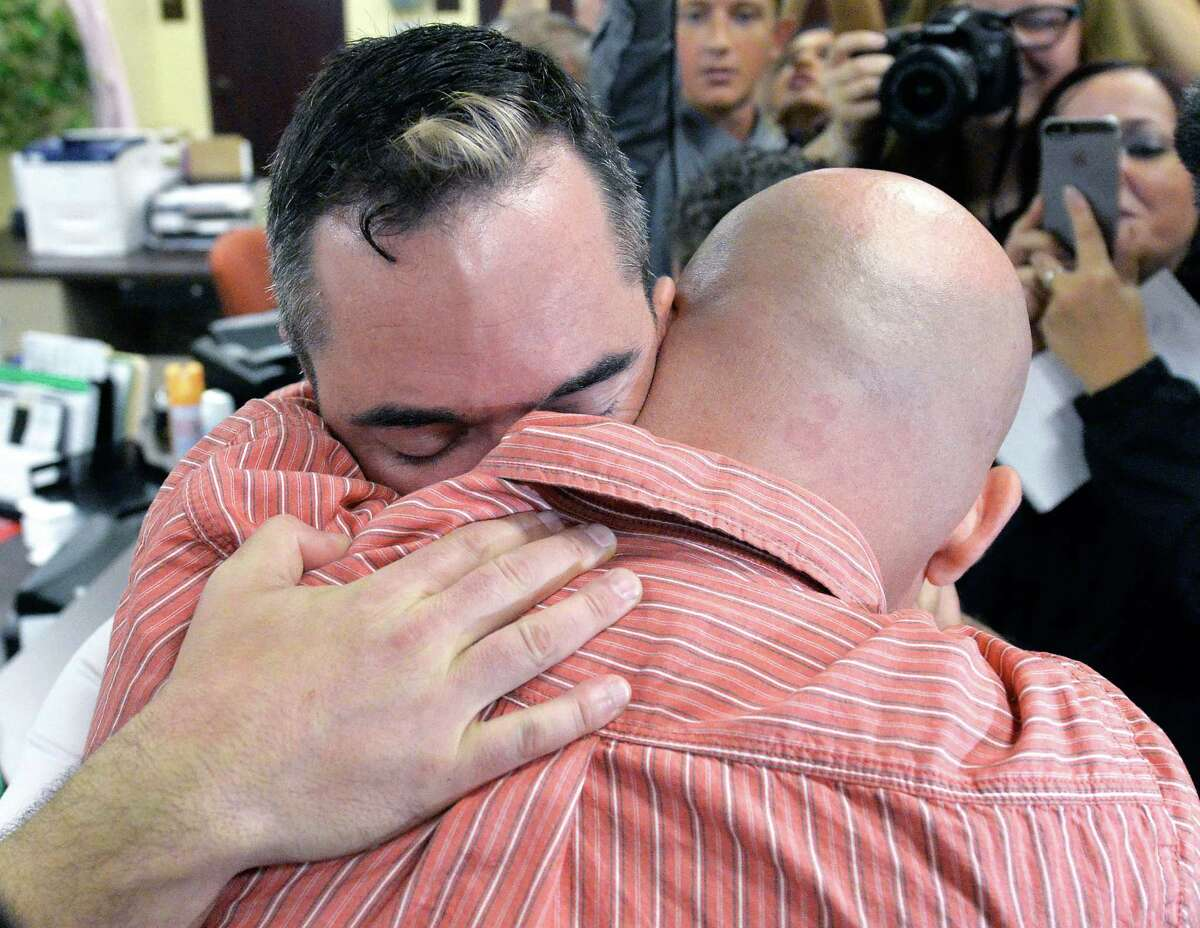 James Yates, left, hugs his partner William Smith Jr., after receiving their marriage license at the Rowan County Judicial Center in Morehead, Ky., Friday, Sept. 4, 2015. Deputy clerk Brian Mason issued the license, congratulating the couple and shaking their hands as he smiled. (AP Photo/Timothy D. Easley) ORG XMIT: KYTE104