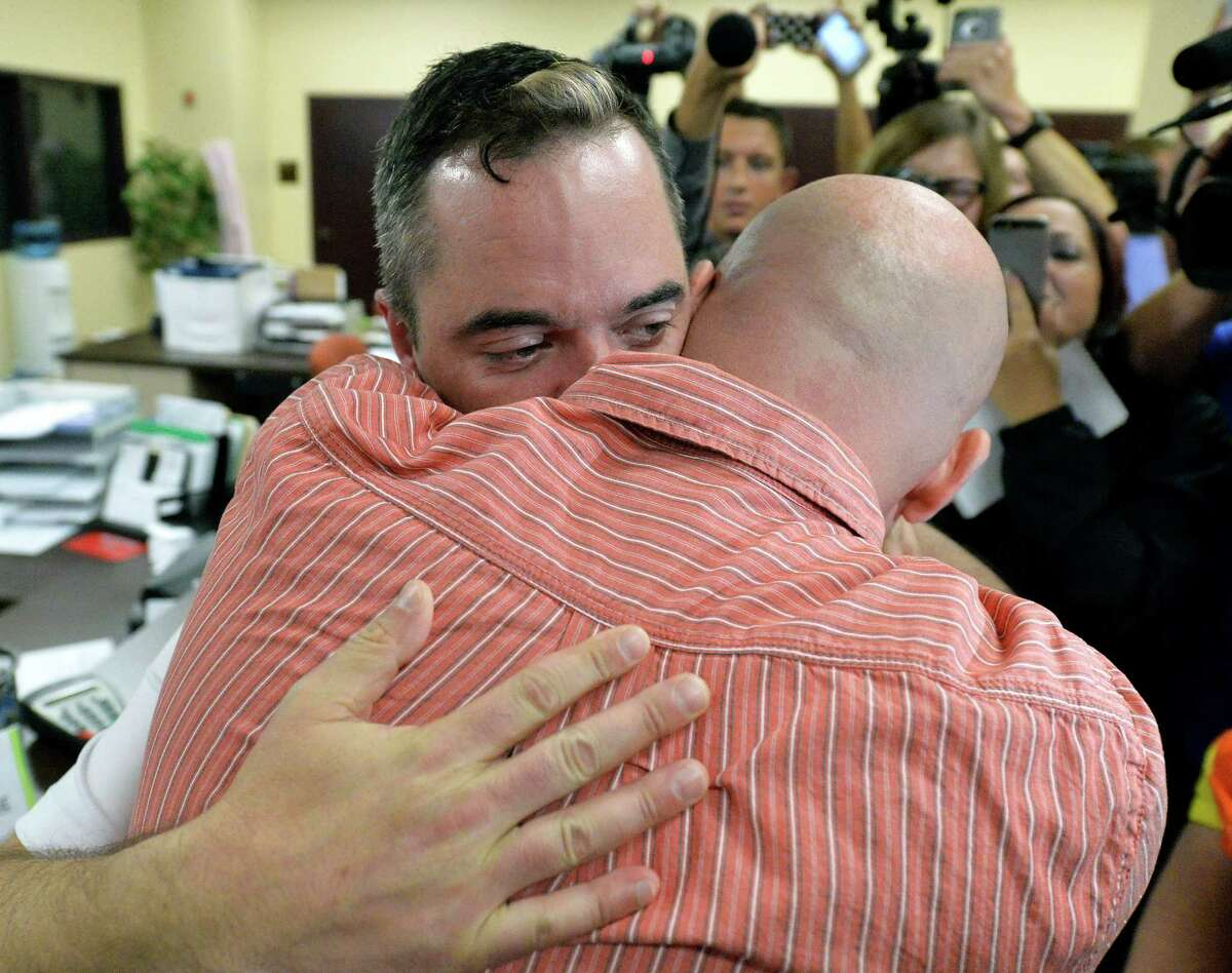 James Yates, left, hugs his partner William Smith Jr., after receiving their marriage license at the Rowan County Judicial Center in Morehead, Ky., Friday, Sept. 4, 2015. Deputy clerk Brian Mason issued the license, congratulating the couple and shaking their hands as he smiled. (AP Photo/Timothy D. Easley) ORG XMIT: KYTE105