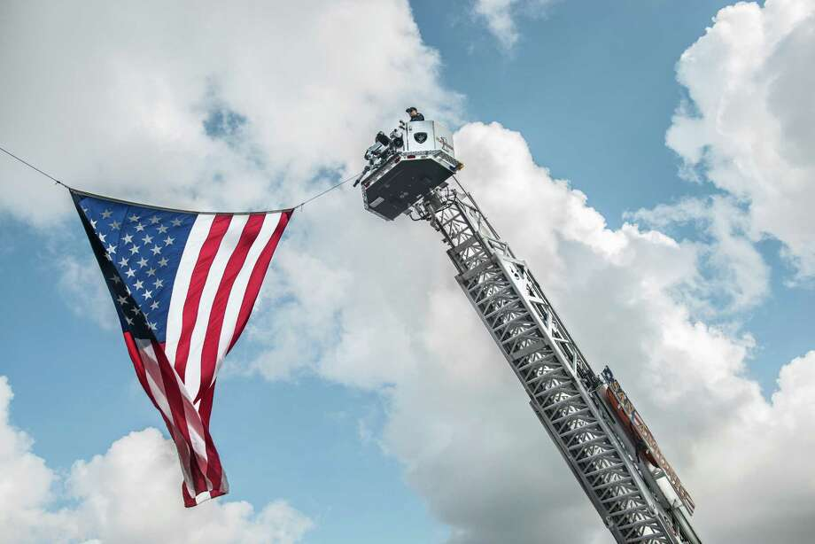 Members of the San Antonio Fire Department hoist an American flag from one of their trucks during the San Antonio local law enforcement tribute for Harris County Sheriff Deputy Darren Goforth at the Alamodome on Friday, September 4, 2015. Deputy Goforth was shot and killed at a gas station on August 28. Photo: Matthew Busch, For The San Antonio Express-News / For The San Antonio Express-News / © Matthew Busch