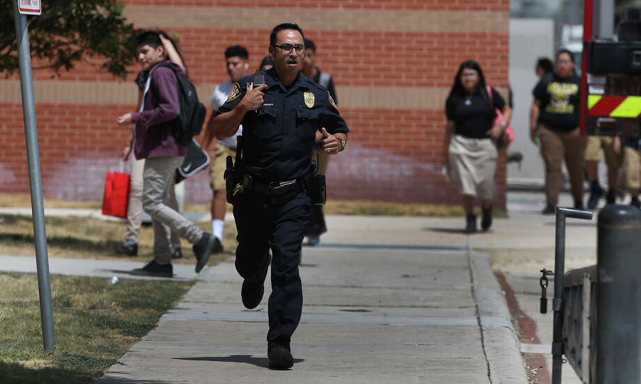 A police officer responds to the call about a student being trapped in a safe at Edison High School. Photo: John Davenport /Express-News / ©San Antonio Express-News/John Davenport