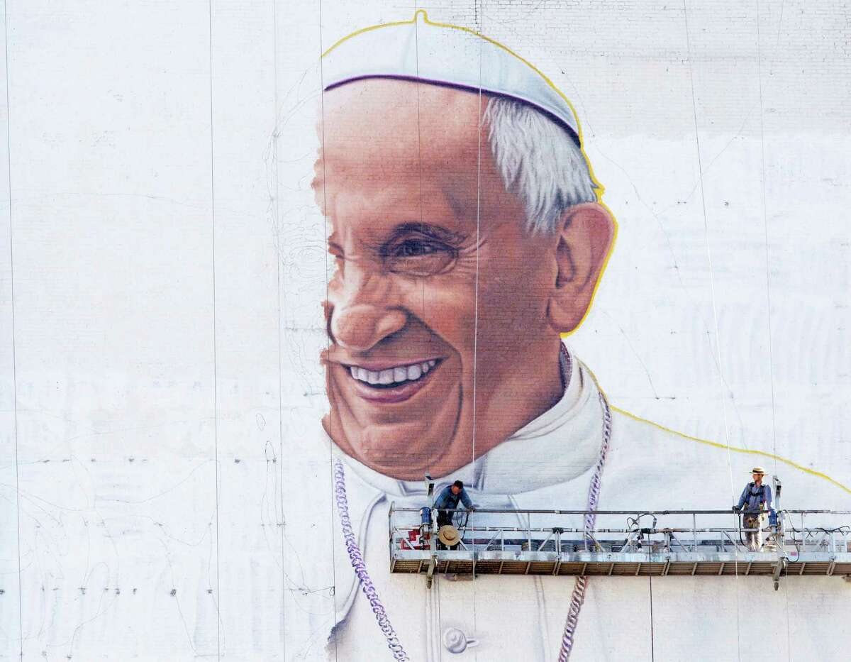 AP10ThingsToSee - Painters move their scaffolding into position to continue painting a mural of Pope Francis on the side of a New York City office building, Friday, Aug. 28, 2015. The Pope visits the U.S. beginning Sept. 22 with stops in Washington D.C., New York and Philadelphia. (AP Photo/Mark Lennihan) ORG XMIT: NC106