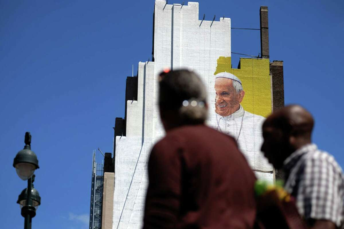 People make their way as a partially completed mural of Pope Francis is seen on the wall of a high-rise building in New York on August 28, 2015. Pope Francis will visit the US on September 22-27, stopping in Washington, DC, New York, and Philadelphia. AFP PHOTO/JEWEL SAMADJEWEL SAMAD/AFP/Getty Images ORG XMIT: 573957341