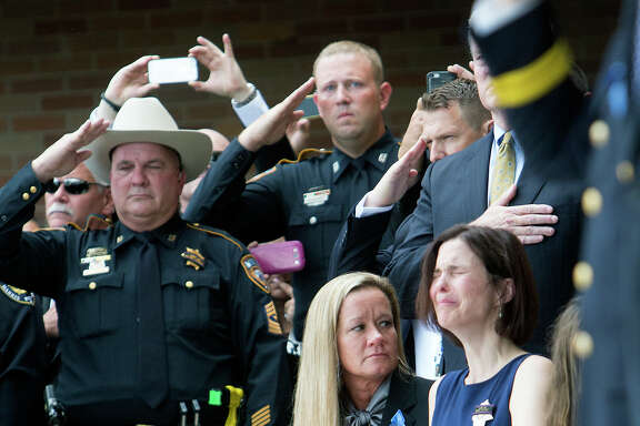 Kathleen Goforth, right, weeps during services Friday for her husband, Harris County Sheriff's Deputy Darren Goforth, at Second Baptist Church. Thousands of mourners attended the service.