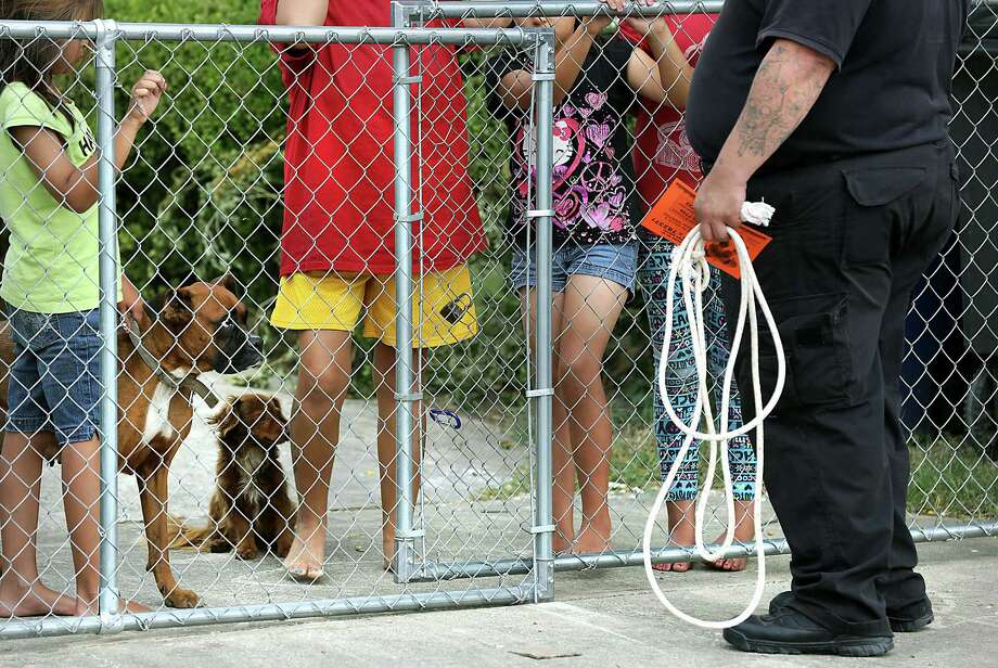 An Animal Care Services officer talks to dog owners who let their pets run loose, during a block walk in neighborhoods on the west side of San Antonio to distribute flyers in outreach efforts to residents through educational instruction, on Friday, July 31, 2015. Photo: Bob Owen, Staff / San Antonio Express-News / San Antonio Express-News
