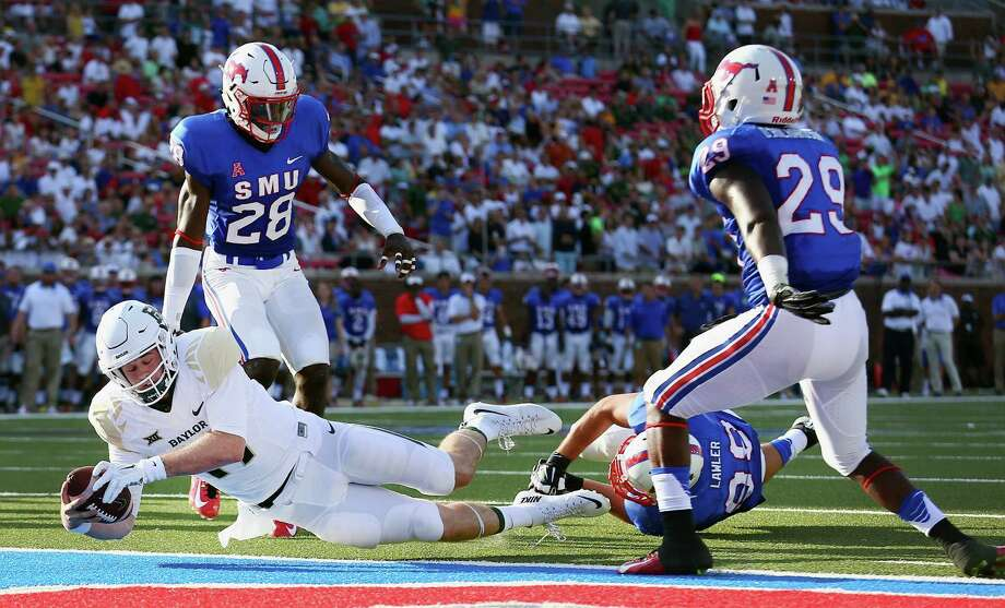 DALLAS, TX - SEPTEMBER 04:  Seth Russell #17 of the Baylor Bears scores a touchdown against Justin Lawler #99 of the Southern Methodist Mustangs, Shakiel Randolph #28 of the Southern Methodist Mustangs and Darrion Richardson #29 of the Southern Methodist Mustangs in the first quarter at Gerald J. Ford Stadium on September 4, 2015 in Dallas, Texas.  (Photo by Tom Pennington/Getty Images) Photo: Tom Pennington, Staff / Getty Images / 2015 Getty Images