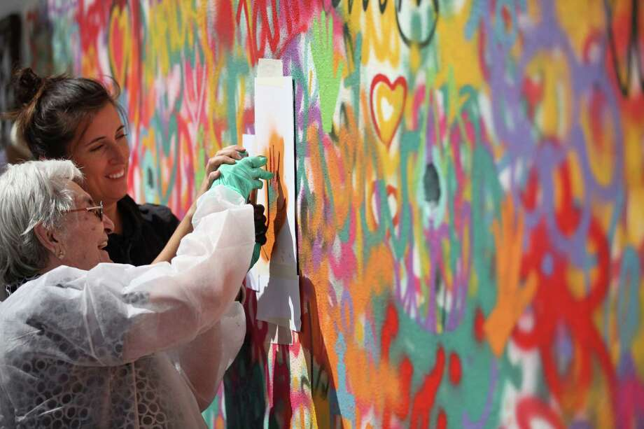 """In this picture taken Sept. 2 2015, Lara Seixo Rodrigues, left, helps Maria do Ceu Pais, 92, stencil the shape of her hand on a wall during a street graffiti workshop in Covilha, Portugal. By the time they have learned enough to start spraying on a wall, they are raring to go. """"They drop their crutches and put aside their walking sticks and jump to it,"""" Lara says. """"They are all capable of having a much more active life."""" (AP Photo/Armando Franca) Photo: Armando Franca, STF / AP"""