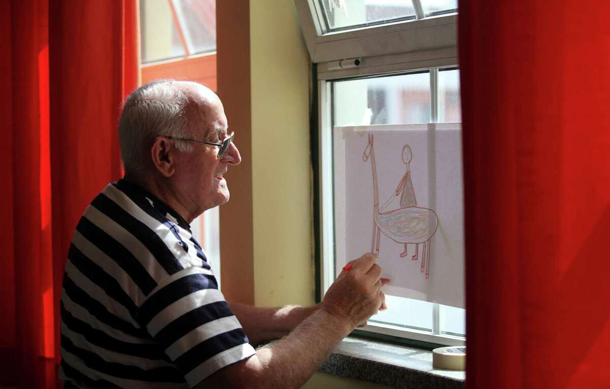 In this picture taken Sept. 1 2015, Raul Lopes Andrade, 82, copies the outline of his drawing onto cardboard to make a stencil during a street graffiti workshop in Covilha, Portugal. Learning how to paint street graffiti, a form of urban art often associated with unruly adolescents, is bringing cheer and a can-do attitude to pensioners in this rural Portuguese city. (AP Photo/Armando Franca)