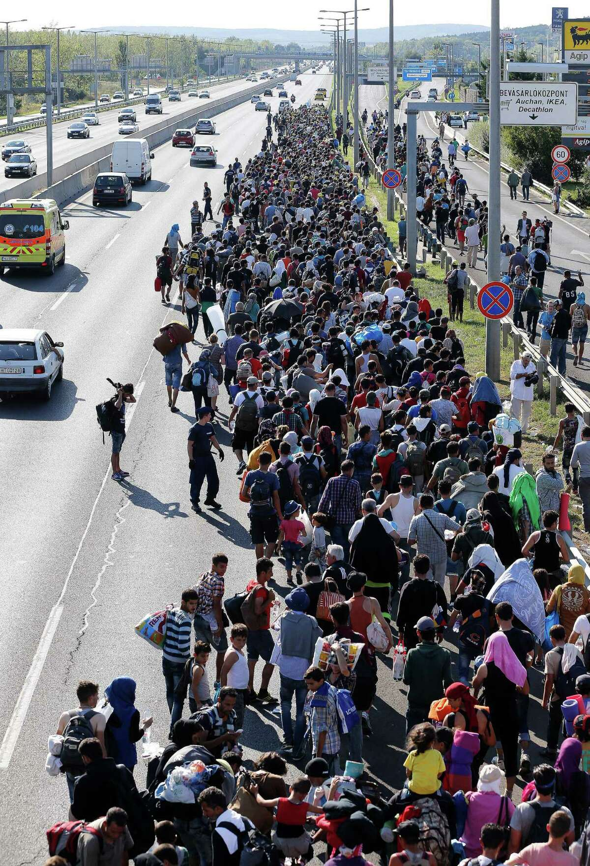 Migrants walk out of Budapest, Hungary, Friday, Sept. 4, 2015. Over 150,000 people seeking to enter Europe have reached Hungary this year, most coming through the southern border with Serbia, and many apply for asylum but quickly try to leave for richer EU countries. (AP Photo/Frank Augstein) ORG XMIT: FAS132
