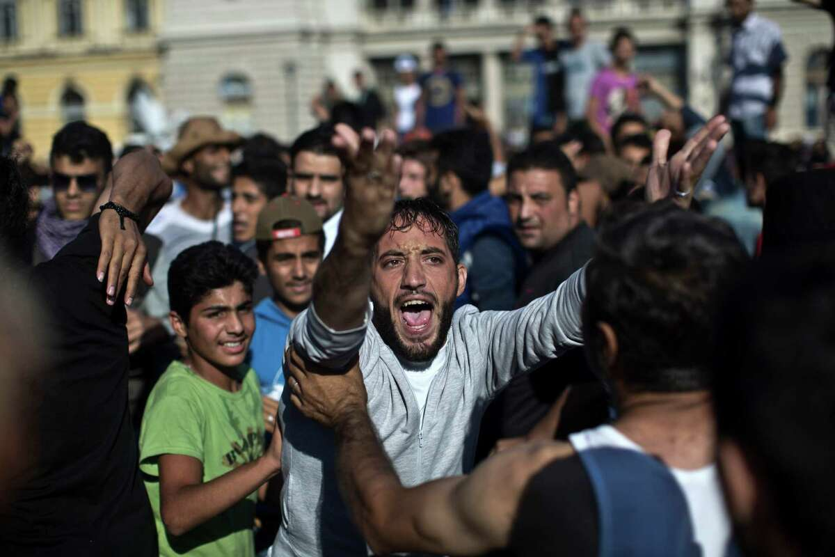 A man shouts during a protest at the Keleti train station in Budapest, Serbia, Friday, Sept. 4, 2015. Hundreds of migrants frustrated at being stuck at two train stations in Hungary set off on foot for Austria on Friday, one group forming a line nearly a half-mile long as they streamed out of Budapest, the other breaking out of a train near a migrant reception center and then running toward the West after overwhelming police. (AP Photo/Marko Drobnjakovic) ORG XMIT: XMD104