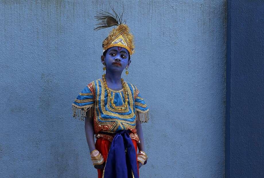 A boy dressed like Hindu Lord Krishna waits to attend celebrations on the eve of Janmashtami at a school in Mumbai, India, Friday, Sept. 4, 2015. The day marks the birth of Krishna. Photo: Rajanish Kakade, Associated Press