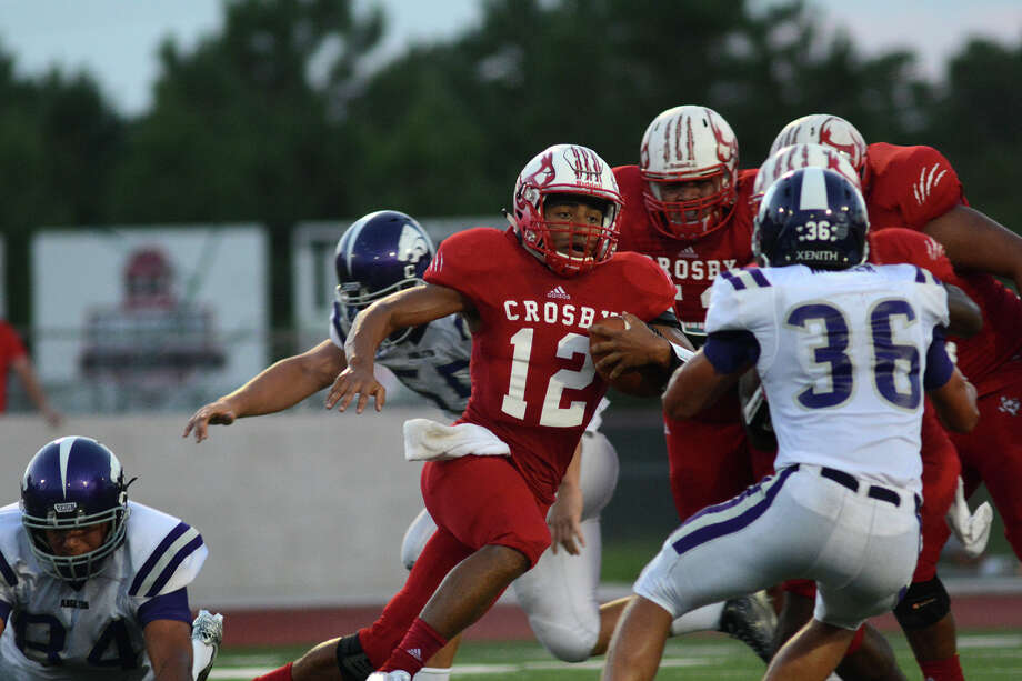 Crosby senior quarterback Tristen Cotton (12) looks for a hole in the Angleton defense, including Wildcat senior saefty Kyle Miller (36) during second quarter action of their matchup at Cougar Stadium in Crosby on Friday, Sept. 4, 2015. (Photo by Jerry Baker/Freelance) Photo: Jerry Baker, For The Houston Chronicle
