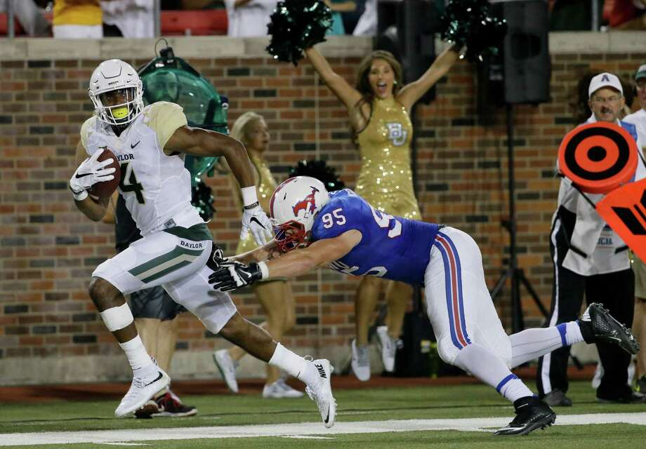 Baylor wide receiver Jay Lee (4) races past SMU defensive lineman Andrew McCleneghen (95) on his way to a 41-yard touchdown reception in the third quarter at Dallas on Friday night. It was his third touchdown catch of the game. Photo: LM Otero, STF / AP