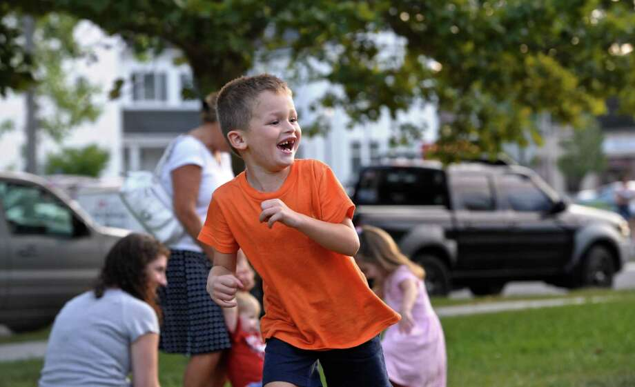 "Joey Corigliano, 5, of Bethel, runs across the front lawn of the Clifford J. Hurgin Municipal Center, in Bethel, while playing with his dad, during the last ""First Friday - Free Outdoor Concert"" of the summer. The series is sponsored by Bethel Arts,  a community-based volunteer group that seeks to promote, build and support the arts and creative culture in Bethel. The concerts were the first Friday night of the month throughout the summer. Friday night, September 4, 2015, in Bethel, Conn. Photo: H John Voorhees III / Hearst Connecticut Media / The News-Times"