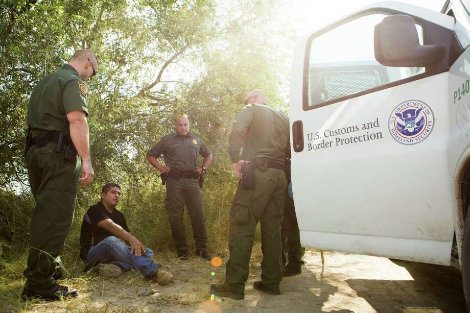 Jason D. Owens, left, Border Patrol agent in charge and Supervisor Border Patrol Agent Jose Luis Perales, center, along with other Border Patrol agents ask questions to an illegal alien that walked to the Border Patrol asking for water. Monday, July 20, 2015, in Cuevitas. ( Marie D. De Jesus / Houston Chronicle ) Photo: Photos By Marie D. De Jesus / Houston Chronicle / © 2015 Houston Chronicle