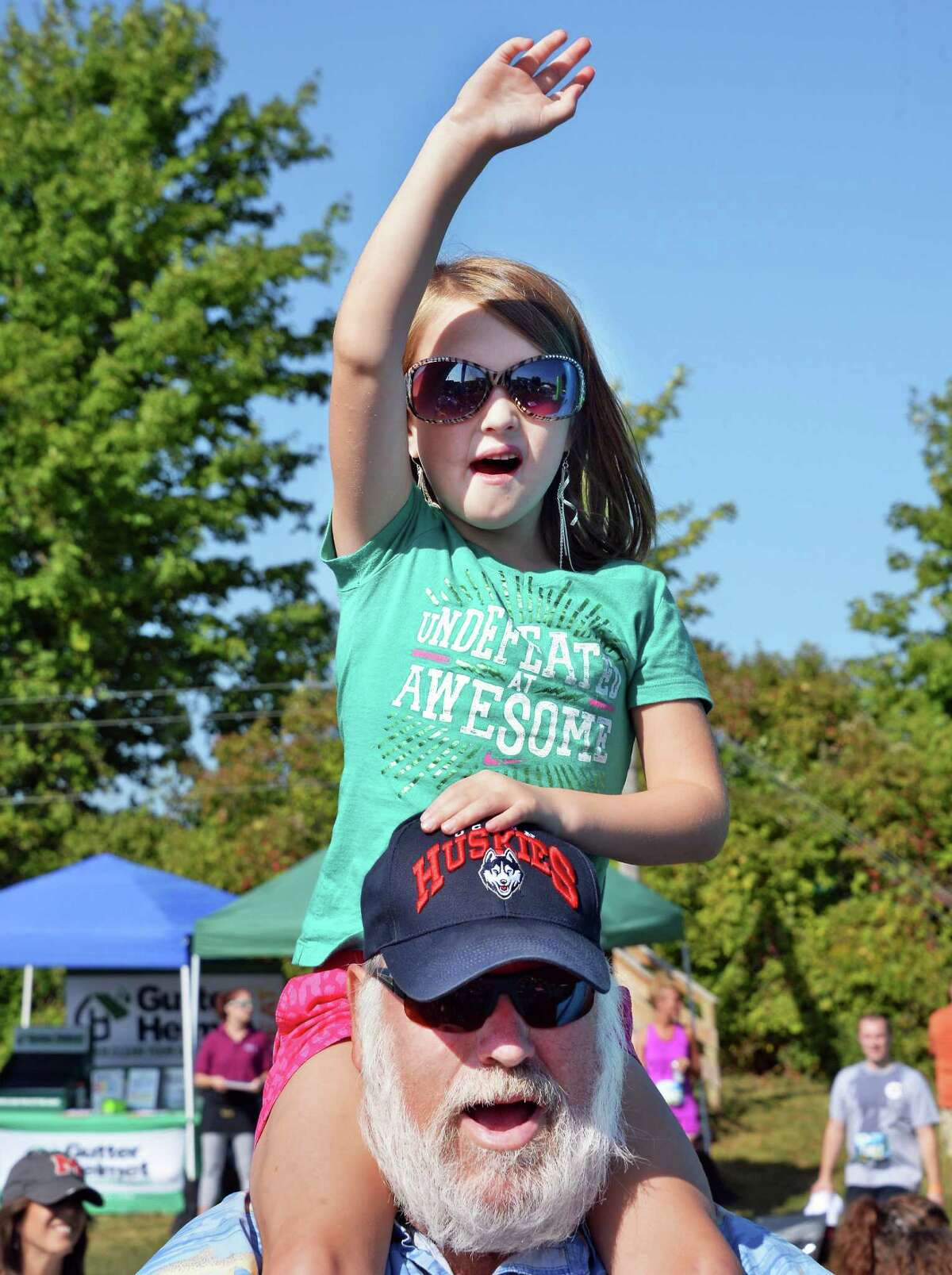 Mark Brown of Warrensburg holds up his granddaughter, 6 -year-old Ahni Brown as she cheers on her parents running the Insane Inflatable 5K Obstacle Fun Run at the Ellms Family Farms Saturday Sept. 5, 2015 in Ballston Spa, NY. (John Carl D'Annibale / Times Union)