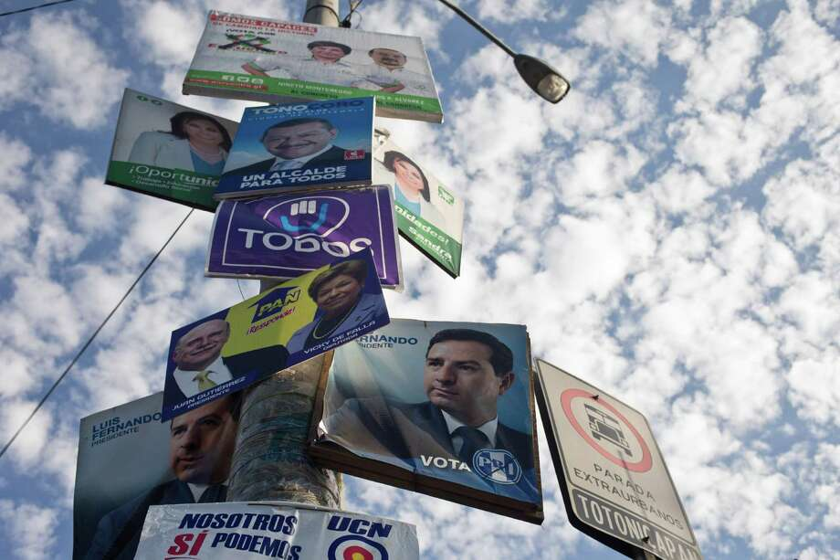 Political campaign posters fill a lamp post in Guatemala City, Saturday, Sept. 5, 2015. Voters go to the polls Sunday for normally scheduled general elections, less than a week after Otto Perez Molina resigned as president. (AP Photo/Esteban Felix) Photo: Esteban Felix, STF / AP