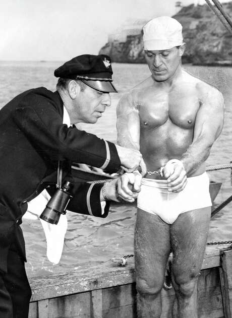 """Elmer """"Skipper"""" Schivo helps fitness guru Jack LaLanne as he prepares to swim to Alcatraz in handcuffs for a television program in July 1955. Photo: Gordon Peters / Gordon Peters / The Chronicle 1955 / ONLINE_YES"""