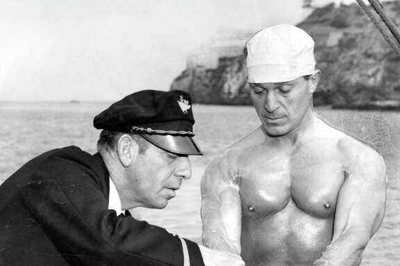"Elmer ""Skipper"" Schivo helps fitness guru Jack LaLanne as he prepares to swim to Alcatraz in handcuffs for a television program in July 1955."