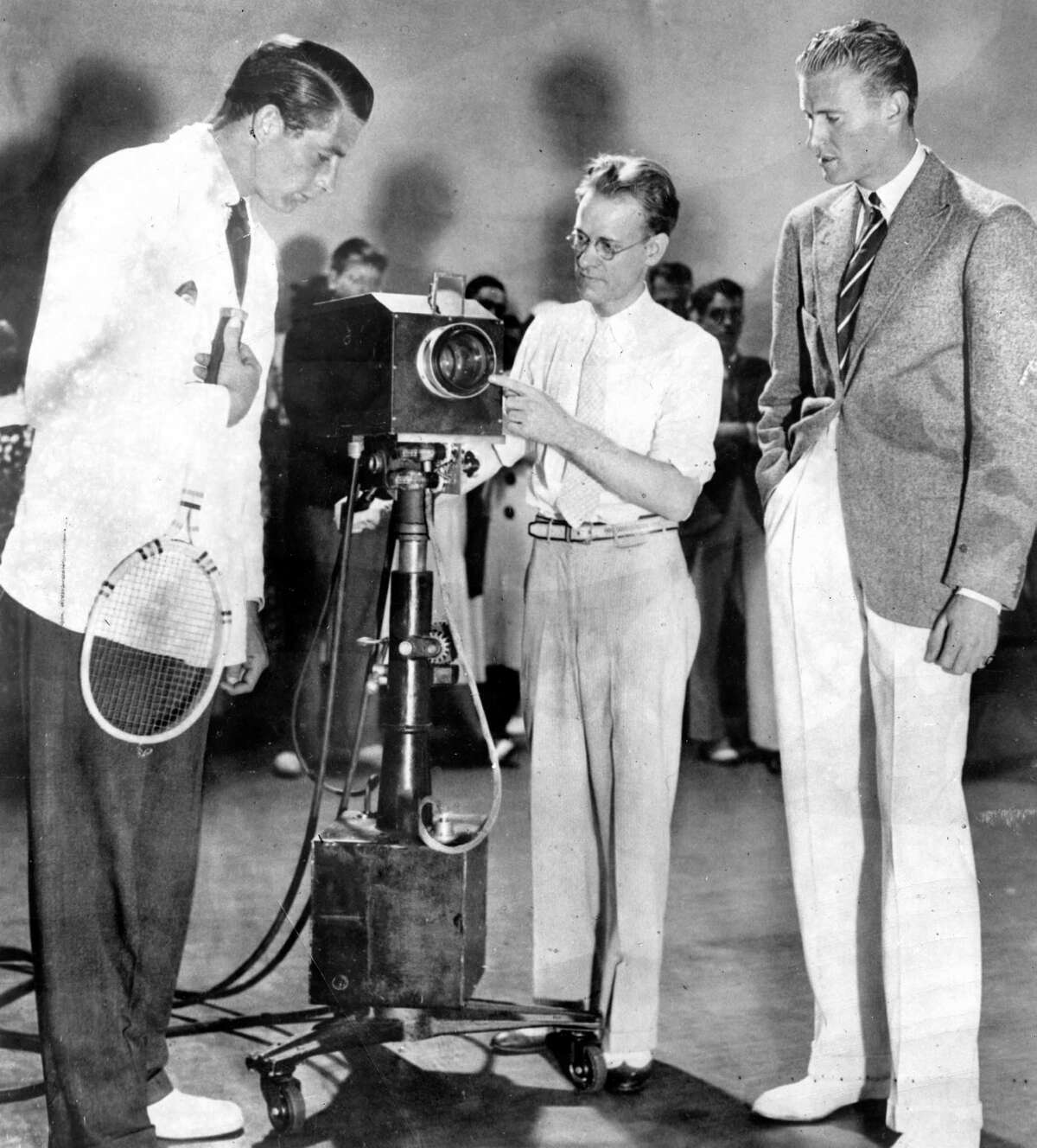 Philo T. Farnsworth who invented the tube leading to television, demonstrates his device to two Davis Cup members Frank Shields (left) and Lester Stoffen (right).