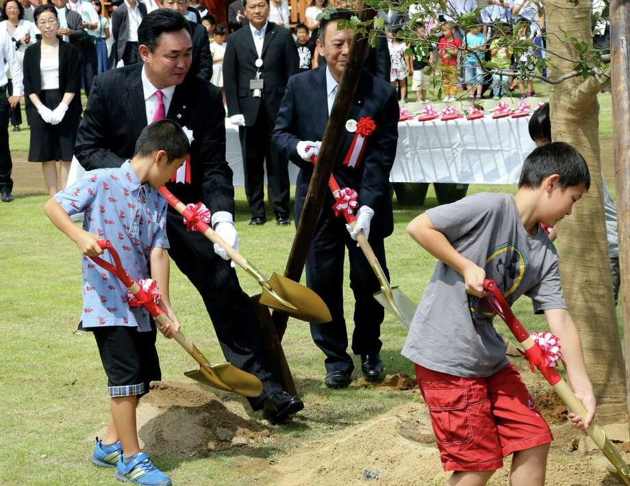Noraha Mayor Yukiei Matsumoto, rear left, plants a tree with children of Naraha residents during an event in Naraha, Fukushima, northern Japan, Saturday, Sept. 5, 2015. The Japanese town of Naraha on Saturday lifted a 2011 evacuation order that sent all its 7,400 residents away after the nearby Fukushima nuclear plant was crippled by a tsunami and spread contamination. (AP Photo/Koji Sasahara) Photo: Koji Sasahara, STF / AP