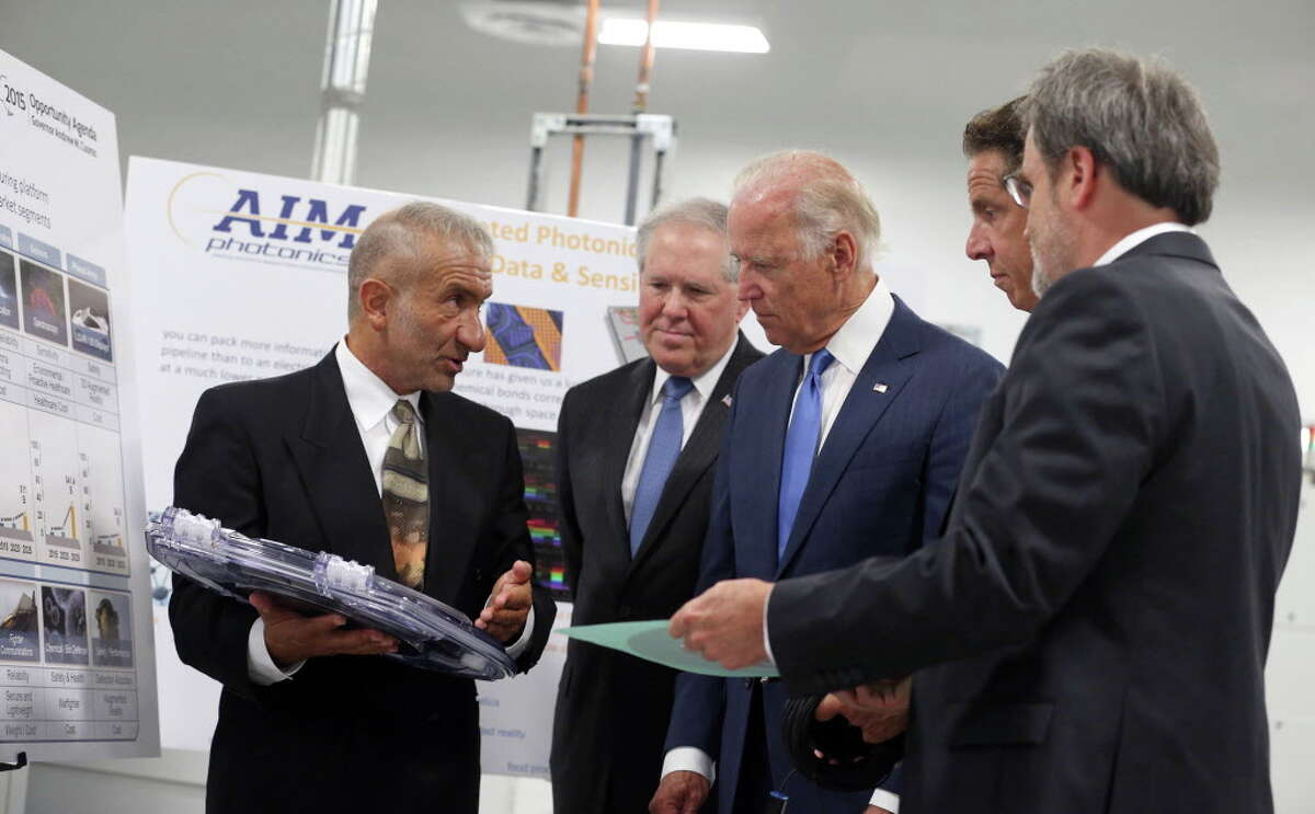 Dr. Alain Kaloyeros, founding President and CEO of SUNY Polytechnic Institute, left, and Michael Liehr, Executive Vice President of Innovation and Technology, Colleges of Nanoscale Science and Engineering, SUNY Polytechnic Institute, right, brief Vice President Joe Biden, center, New York Governor Andrew Cuomo, second from right, and Under secretary Frank Kendall, as they visit SUNY Poly Canal Ponds during the official announcement of the Department of Defense awarding a $110 million to help create the new American Institute for Manufacturing Integrated Photonics Monday, July 27, 2015, in Rochester, NY. (Shawn Dowd/Democrat & Chronicle via AP) ORG XMIT: NYROD102
