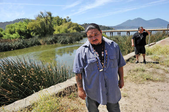 Rob Morgan, Koi Nation tribal historical preservation officer, describes the looting of Native American sites, with fellow tribal official Dino Beltran behind him on the shore of Clear Lake.